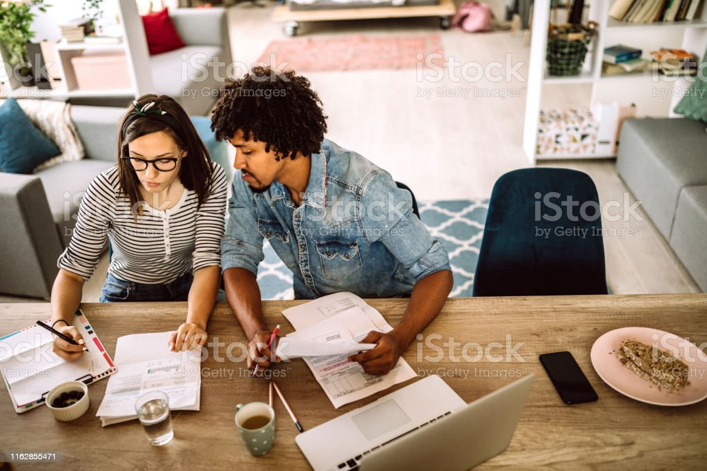 Modern married multi-ethnic young couple calculating financial bills...