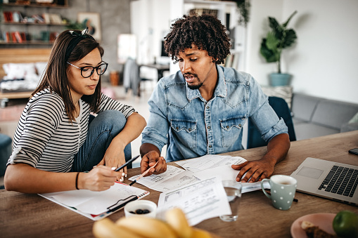 Modern married multi-ethnic young couple calculating financial bills at home