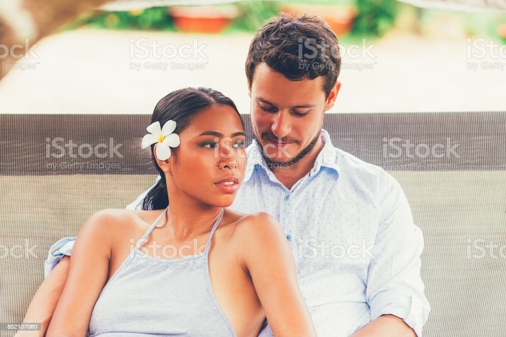 Multi-ethnic Couple Relaxing on Patio Swing stock photo