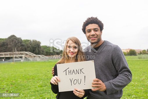 istock Multiethnic Couple Saying Tahnk You with a Board 532136307