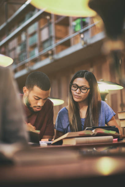 multi-ethnic couple studying in library - compagni scuola foto e immagini stock
