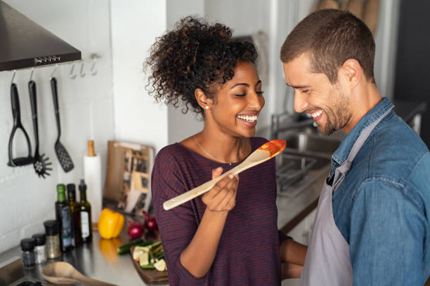 multiethnic couple tasting food from wooden spoon - assaggiare foto e immagini stock