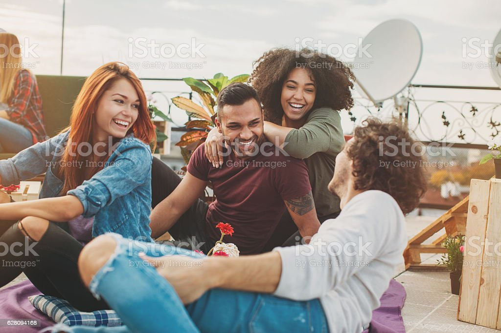 Multi-ethnic couples chatting on the rooftop stock photo