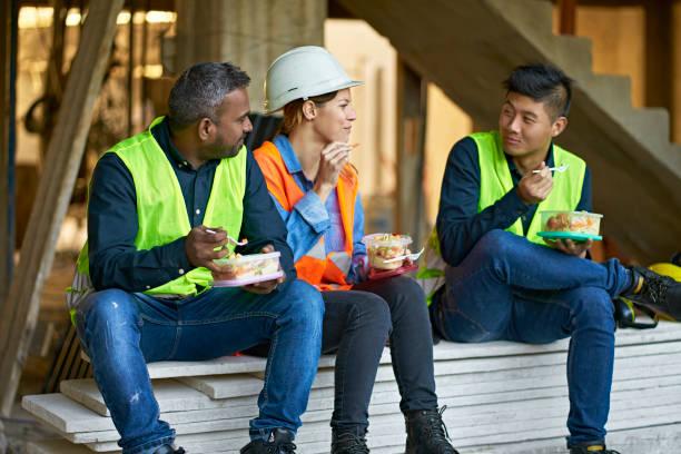Multiethnische Mitarbeiter essen Mittagessen vor Ort – Foto