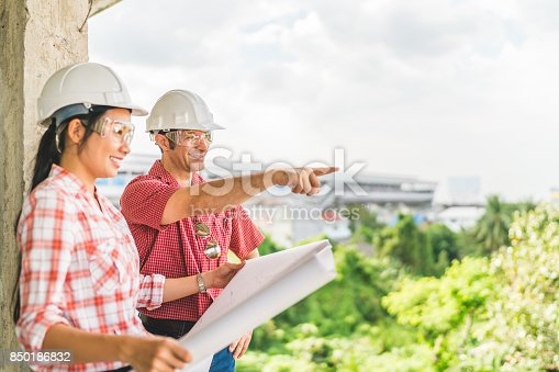 681142982 istock photo Multi-ethnic diverse couple of happy civil engineer work together on building blueprint. Architect interior industry, teamwork meeting, outdoor construction site survey, or consultant advice concept 850186832