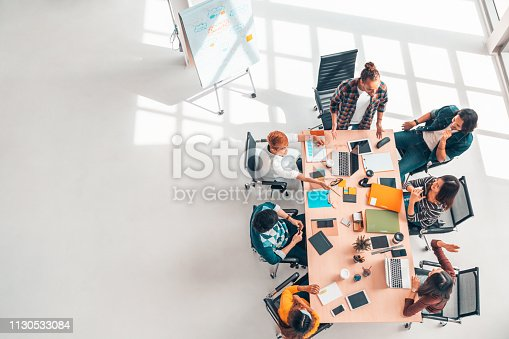 Multiethnic diverse group of business coworkers in team meeting discussion, top view modern office with copy space. Partnership professional teamwork, startup company, or project brainstorm concept
