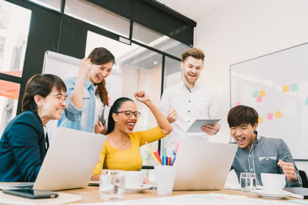 Multiethnic diverse group of coworkers celebrate together with laptop and tablet. Creative team, casual business colleague, college student at modern office. Startup, teamwork, success project concept stock photo