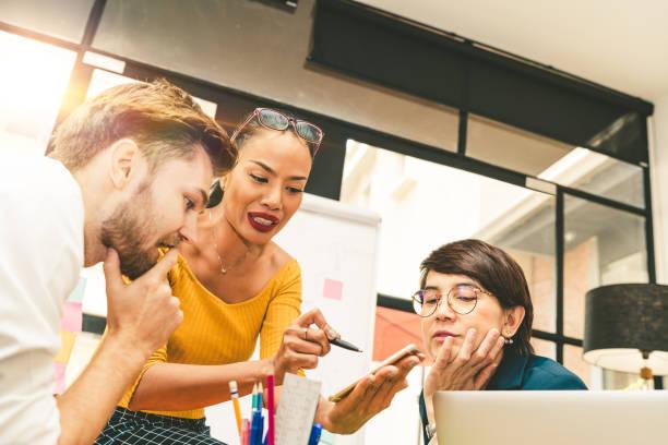 Multiethnische vielfältige Gruppe von kreativen Team, Gelegenheits-Geschäftsleute oder College-Studenten in strategischen Treffen oder Projekt Brainstorming-Diskussion im Büro, mit dem Smartphone. Startup- oder Teamwork-Konzept – Foto