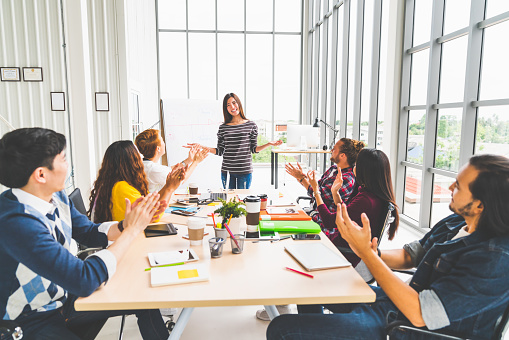 istock Multiethnic diverse group of creative team or business coworker clapping hands in project presentation meeting leading by Asian woman. Success teamwork, modern office work, or startup company concept 1018416482