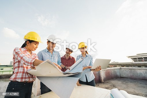 istock Multiethnic diverse group of engineers or business partners at construction site, working together on building's blueprint, architect industry or teamwork concept 681142982