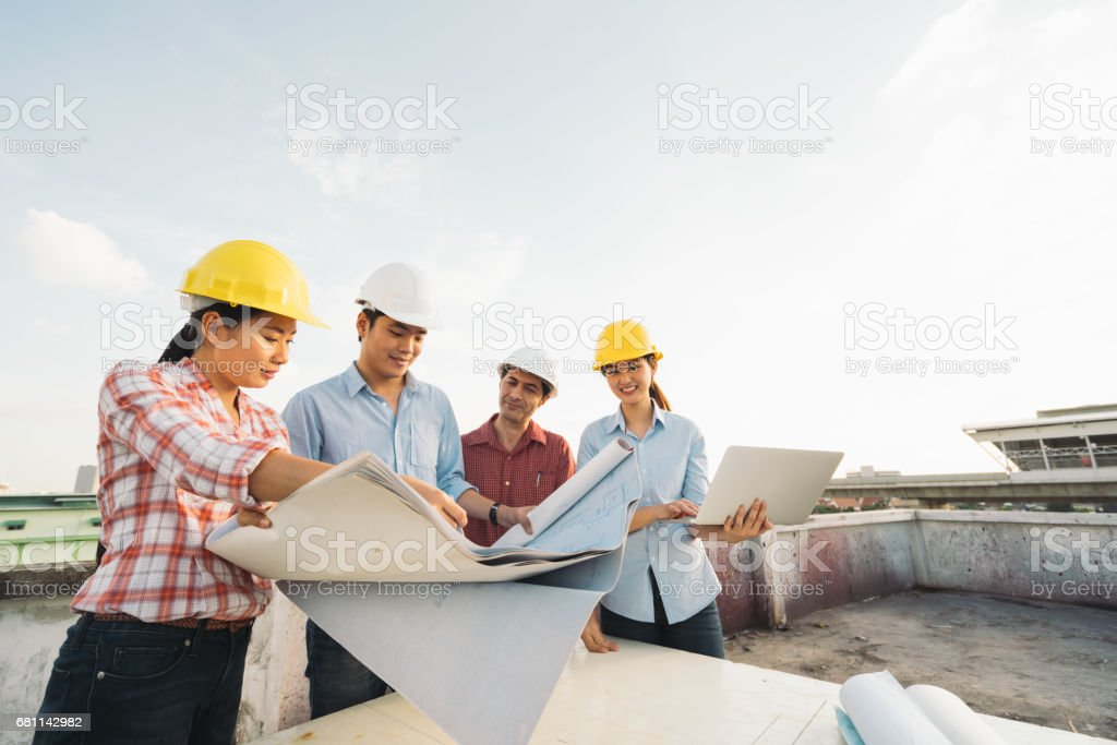 Multiethnic diverse group of engineers or business partners at construction site, working together on building's blueprint, architect industry or teamwork concept stock photo