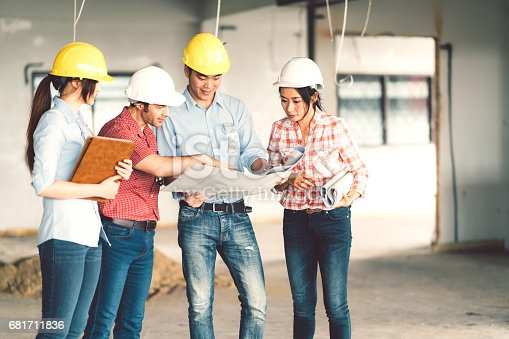 1166176793 istock photo Multiethnic diverse group of engineers or business partners at construction site, working together on building's blueprint, architect engineering industry or teamwork concept 681711836
