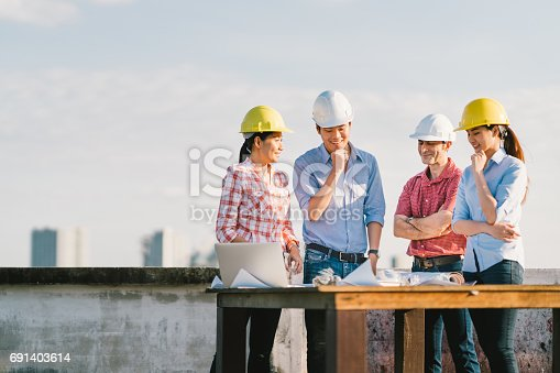 1166176793 istock photo Multiethnic diverse group of engineers or business partners at construction site, working together on building's blueprint, architect industry or teamwork concept 691403614