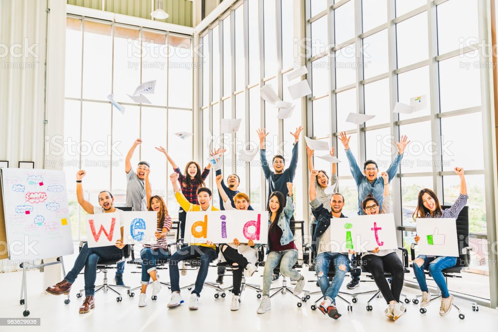 Multiethnic diverse group of happy business people cheering together, celebrate project success with papers written We did it. Coworker teamwork, team achievement, or small business startup concept stock photo