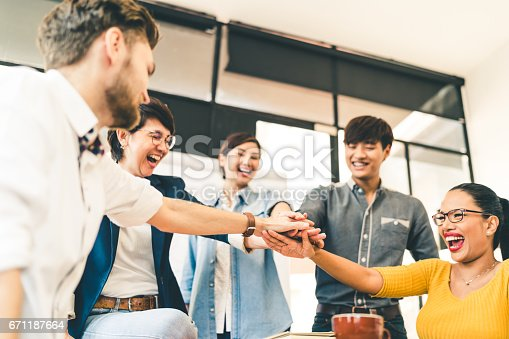 istock Multiethnic diverse group of happy colleagues join hands together. Creative team, casual business coworker, or college students in project meeting at modern office. Startup or teamwork concept 671187664