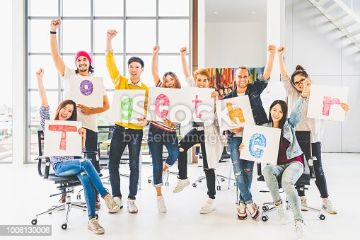 istock Multiethnic diverse group of office coworkers or creative team cheering and celebrating, holding letter banner papers written together word. Colleague partner teamwork, team building, empowerment, or friendship togetherness concept 1006130006