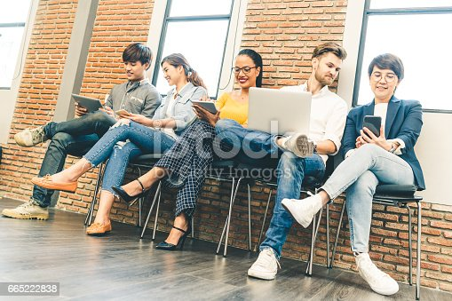 istock Multiethnic diverse group of young and adult people using smartphone, laptop computer, digital tablet together. Modern lifestyle with infomation technology gadget, education, social network concept 665222838