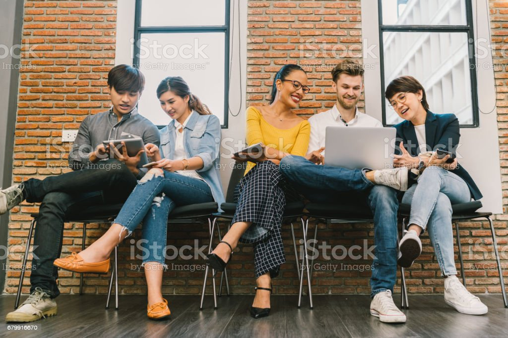 Multiethnic diverse group of young and adult people using smartphone, laptop computer, digital tablet together. Modern lifestyle with information technology gadget, education, social network concept stock photo