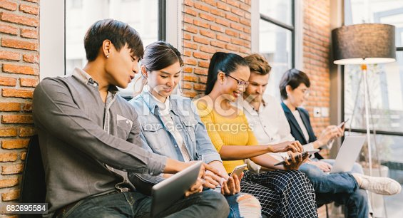 istock Multiethnic diverse group of young and adult people using smartphone, laptop computer, digital tablet together. Modern lifestyle with information technology gadget, education, social network concept 682695584