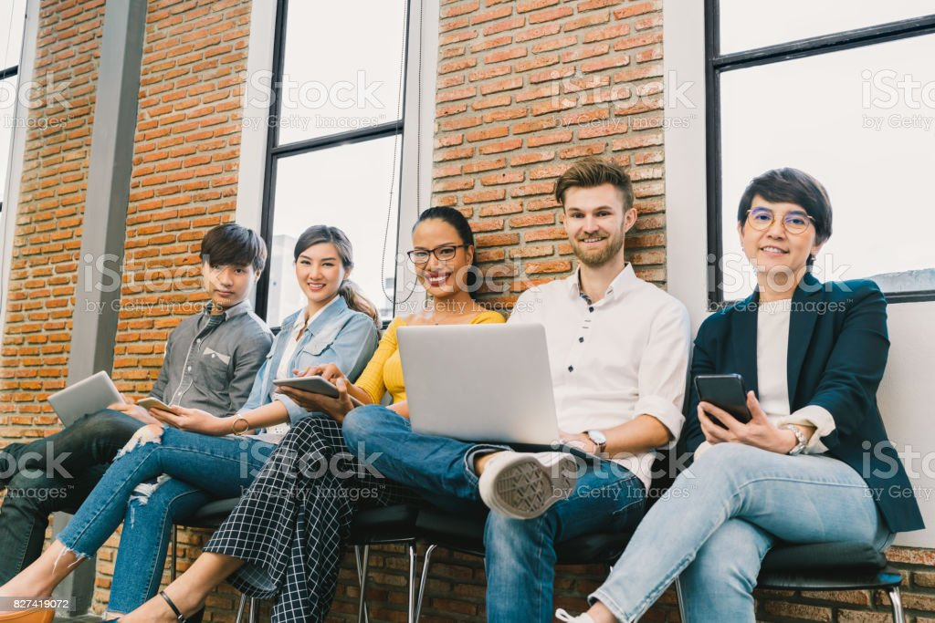 Multiethnic diverse group of young and adult people using smartphone, notebook computer, digital tablet together. Modern lifestyle with information technology gadget, education, social network concept stock photo