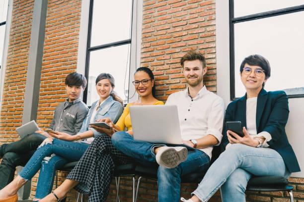 一緒にスマート フォンやノート パソコン、デジタル タブレットを使用して人の若者や大人の多民族の多様なグループです。情報技術ガジェット、教育、社会的ネットワークの概念と現代のライフ スタイル - フリーランス ストックフォトと画像