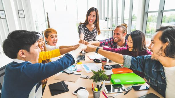 多民族の多様なグループのオフィスの同僚、ビジネス パートナーの結合手の拳では近代的な創造的なオフィスにバンプします。同僚のパートナーシップ チームワーク、スタートアップ企業� - 楽しさ ストックフォトと画像