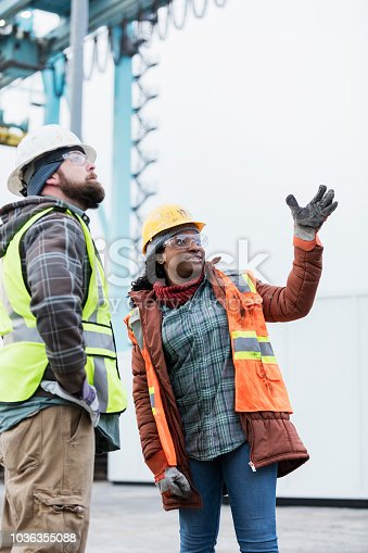 Two multi-ethnic dock workers having a discussion at a shipping port, a gantry crane out of focus in the background. They are wearing hardhats, safety glasses and reflective clothing. A mid adult African-American woman is talking and pointing upward while her male coworker stands with his hands on his hips, listening.