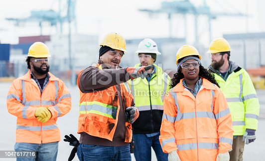 A multi-ethnic group of five dock workers, including an African-American woman, walking and talking. There are gantry cranes and cargo containers in the background. They are wearing hardhats, safety glasses and reflective clothing. The focus is on the  mature Hispanic man in his 40s talking and pointing and the woman who is listening.