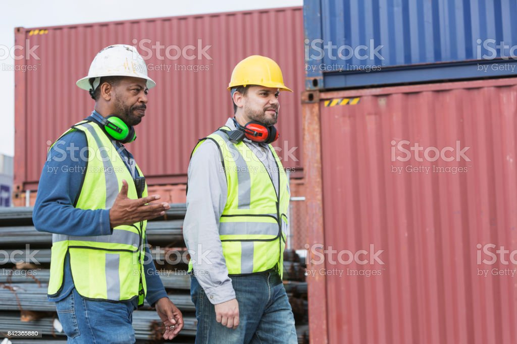 Multi-ethnic dock workers at shipping port stock photo