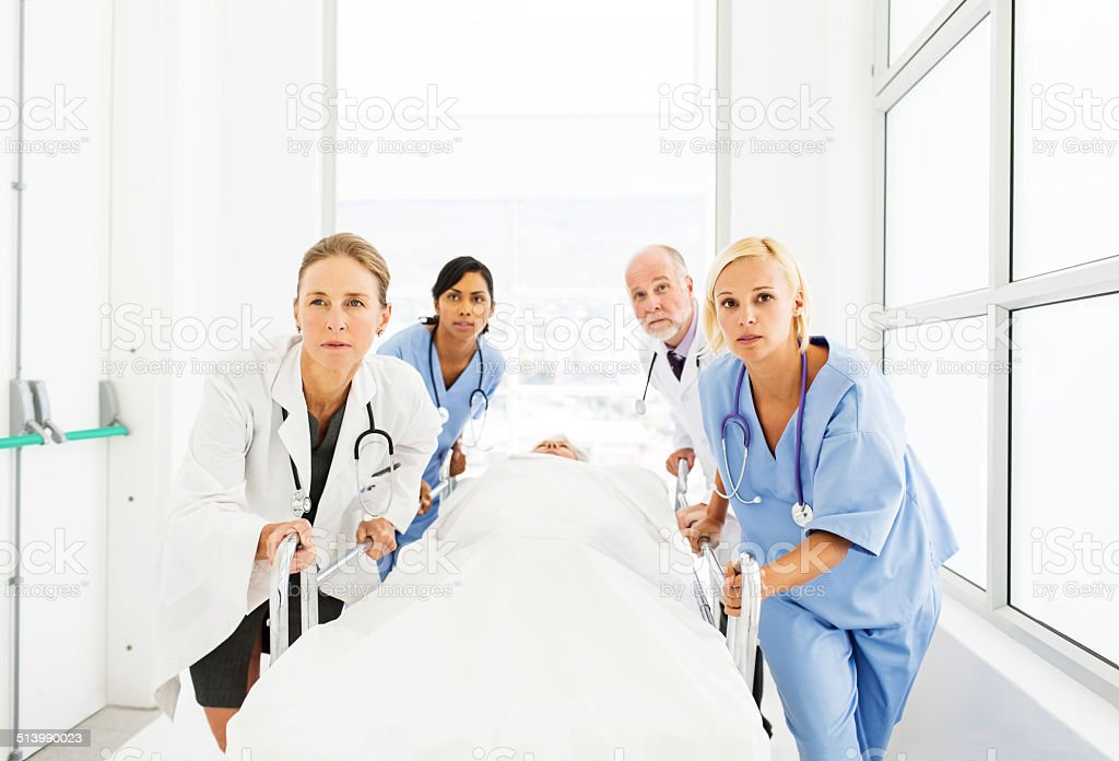 Multiethnic Doctors And Nurses Pushing Patient On Stretcher stock photo