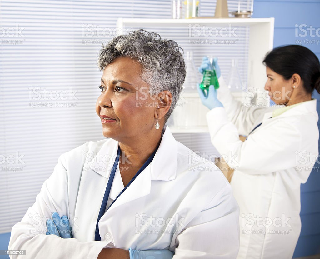Multi-ethnic doctors,scientists. One looking away, other inspecting beaker. royalty-free stock photo