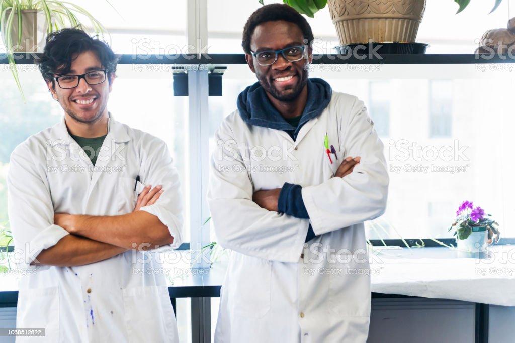 Multi-ethnic duo of professors in college science laboratory. stock photo