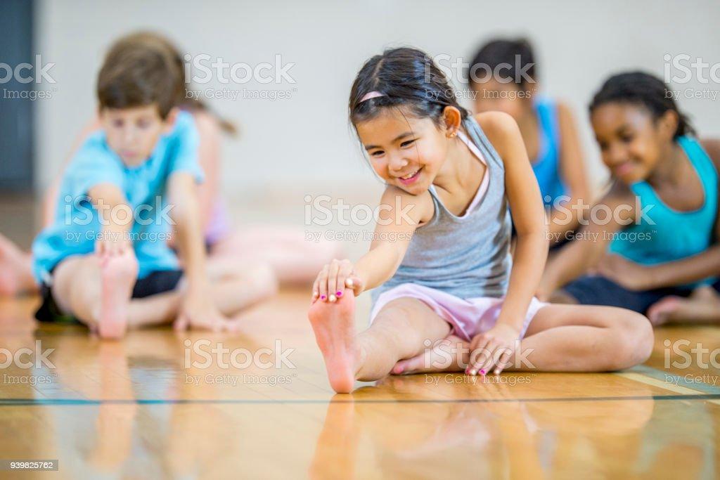 Multi-ethnic elementary age group stretching stock photo