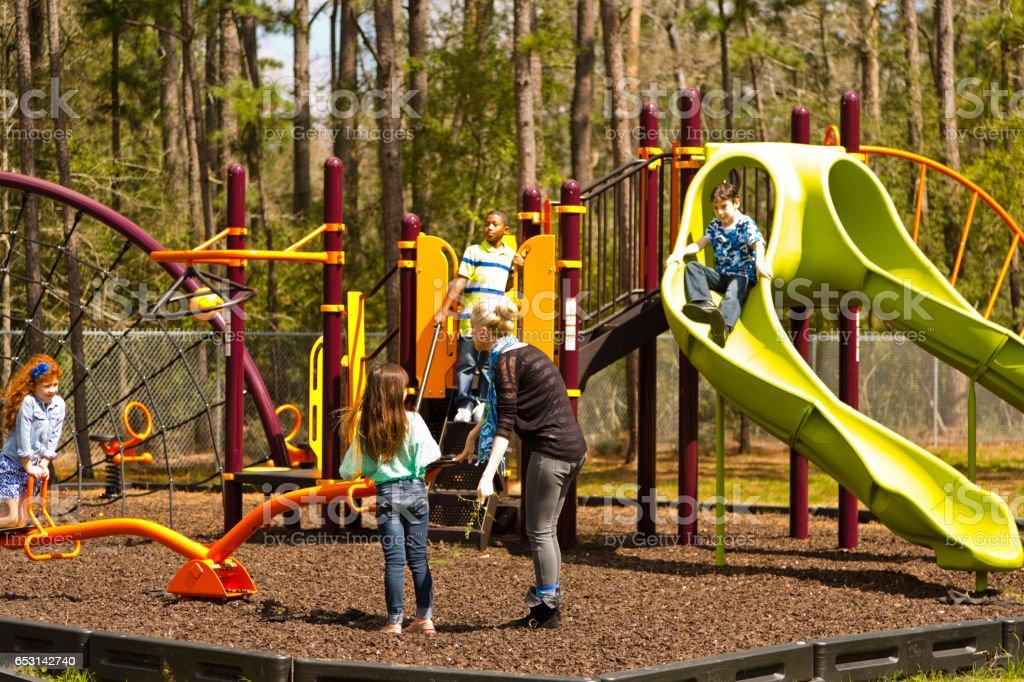 Multi-ethnic elementary school children playing on playground at park. stock photo