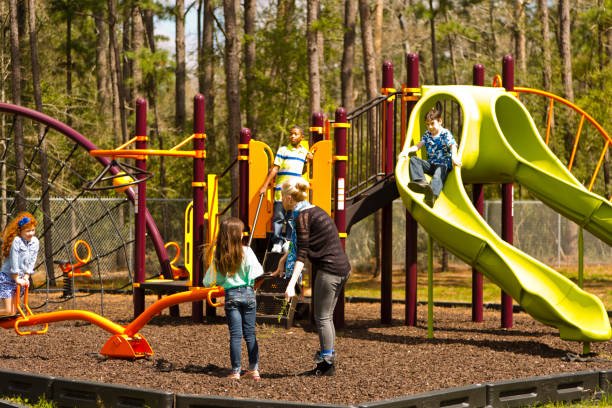 multi-ethnic elementary school children playing on playground at park. - recess stock photos and pictures