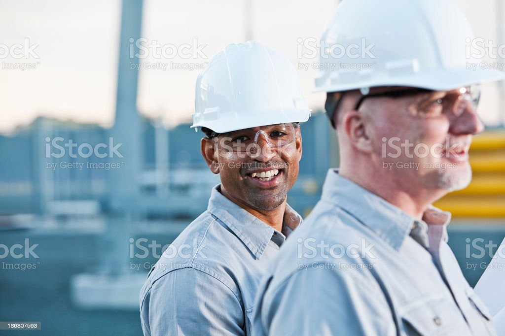 Multi-ethnic engineers at industrial site stock photo