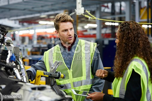 941796726istockphoto Multi-ethnic engineers discussing over car chassis 1076609212