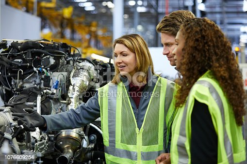 941796726istockphoto Multi-ethnic engineers examining car chassis 1076609254
