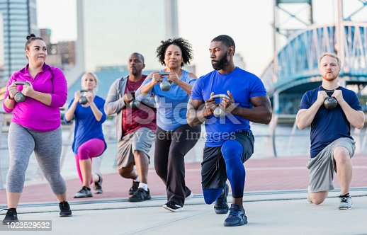 A mid adult African-American man in his 30s, wearing a blue shirt, leading a multi-ethnic exercise class of mixed ages. The oldest in the group is a senior woman in her 60s, in the middle next to the instructor. They are lifting kettle bells, doing lunges. They are outdoors on a plaza on a city waterfront.