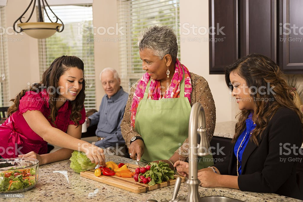 Multiethnic family and friends in kitchen stock photo