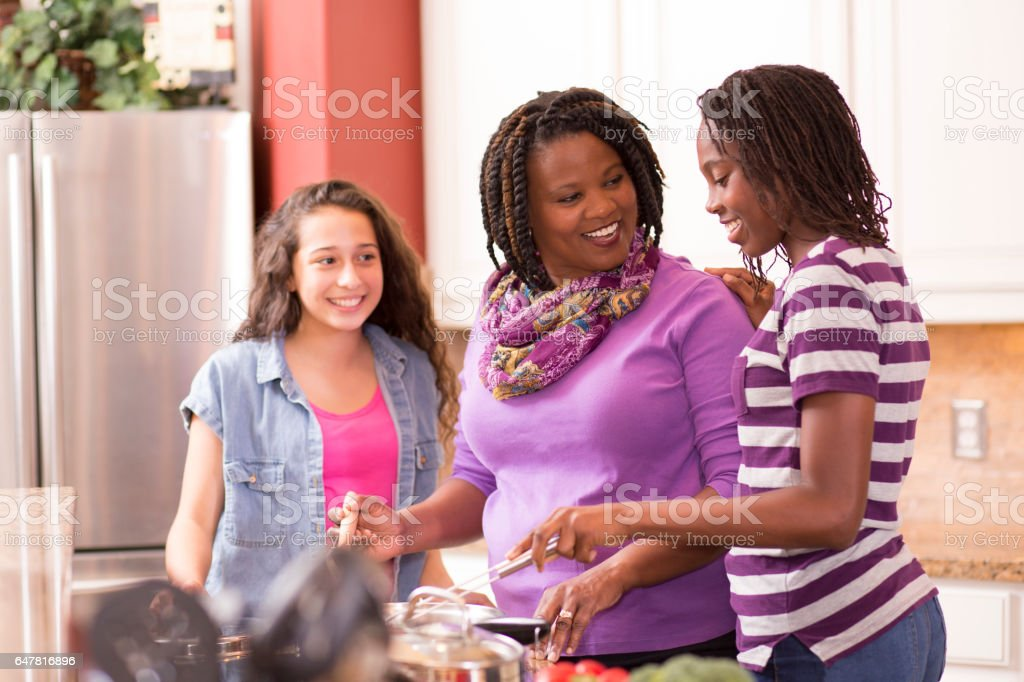 Multi-ethnic family at home cooking together in kitchen. stock photo