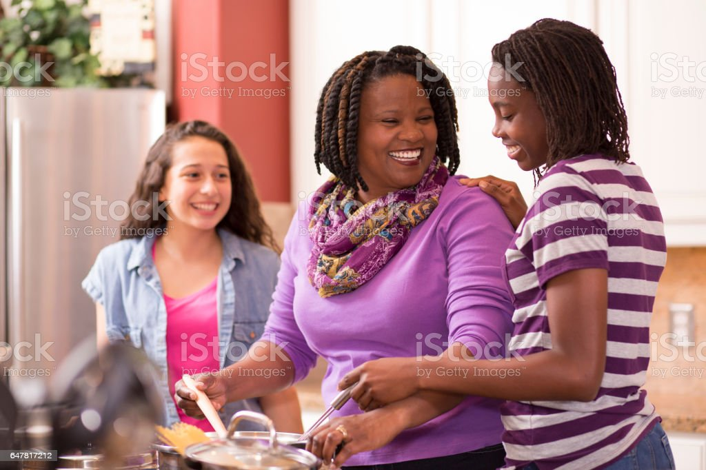 Multi-ethnic family at home cooking together in kitchen. royalty-free stock photo