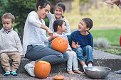 Mom carves and decorates pumpkins with her young children. They're hanging out on a patio outside.