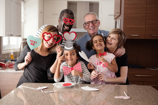 Multi-Ethnic family doing photobooth during Valentine's day stock photo