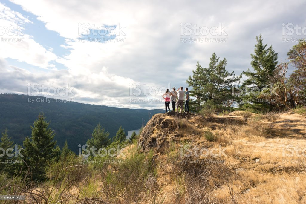 Multi-Ethnic Family Group of Hikers Looking over Viewpoint on Mountaintop stock photo