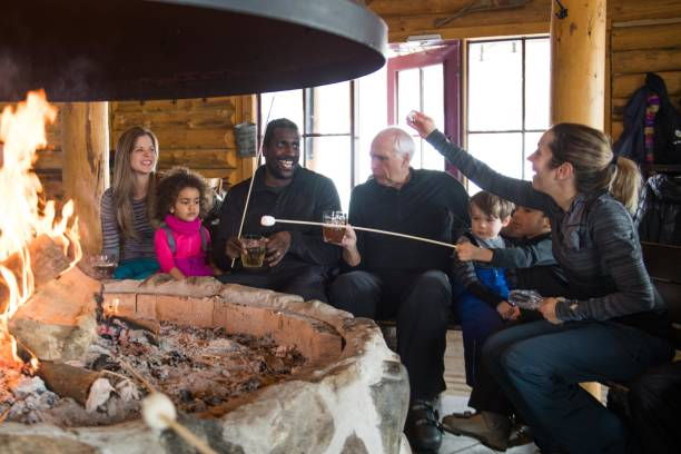 Multi-ethnic family in a ski cottage, apres-ski break Black father with his family and friends in a ski resort during apres-ski in an afternoon day in a small town in Quebec Canada. It was their first time skying. They eat sausage and marshmallow. The color and horizontal photo was taken in Quebec Canada. ski resort stock pictures, royalty-free photos & images