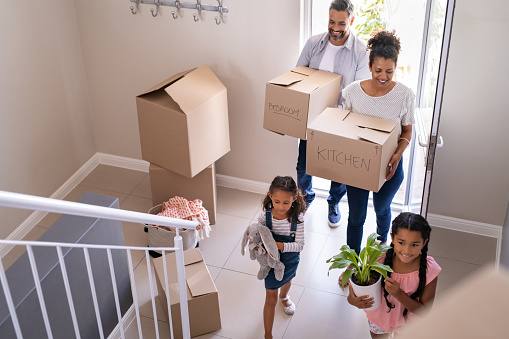 Ethnic family with two children carrying boxes and plant in new home on moving day. High angle view of happy smiling daughters helping mother and father with cardboard boxes in new house. Top view of excited kids having fun walking up stairs running to their rooms while parents holding boxes.