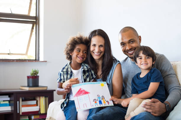 """Multiethnic family on sofa Proud parents showing family painting of son sitting on sofa at home. Smiling mother and father with children""""u2019s drawing of a new home. Black little boy with his family at home showing a painting of a happy multiethnic family. mixed race person stock pictures, royalty-free photos & images"""
