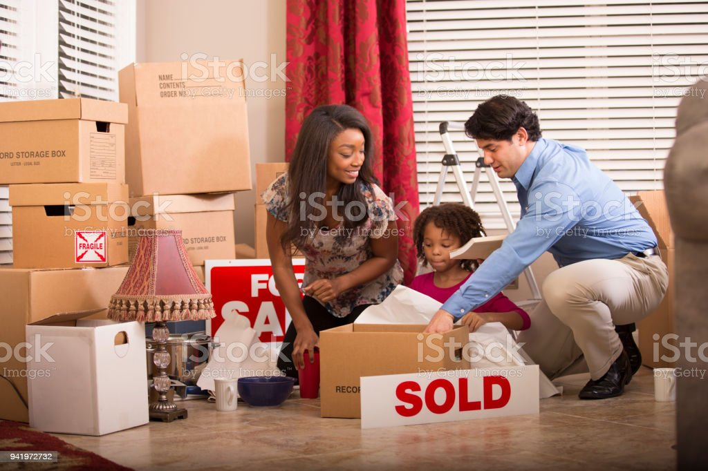 African and Latin descent family members pack or unpack boxes in new...