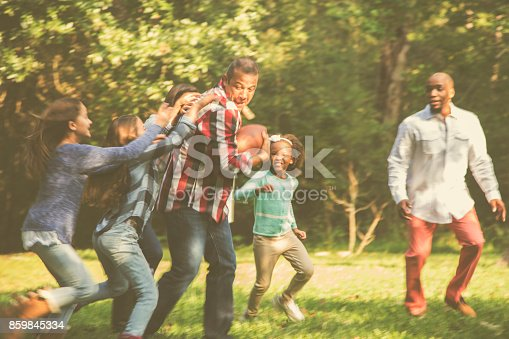 istock Multi-ethnic family playing football in backyard at Thanksgiving. 859845334